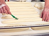 A baker scoring baguettes