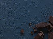 Pieces of chocolate on a blue surface