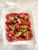Beef carpaccio with cherry tomatoes, rocket and Parmesan cheese