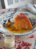 A slice of sponge cake with orange syrup on a plate