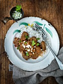 Indian kidney curry with chopped onions and coriander on a bed of rice