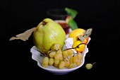 An autumnal arrangement of fruit featuring grapes, a quince and apples in a porcelain bowl