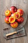 Fresh nectarines in a wire basket, one halved (seen from above)