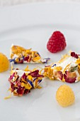 Goat's cheese corners with edible flowers and fresh raspberries