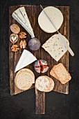 A cheese platter featuring Havarti, Brie, Danish caraway cheese, blue cheese, figs, crackers and nuts