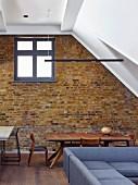 Offener Wohnraum mit Sichtmauerwerk und Giebelfenster in ehemaligem Industriegebäude