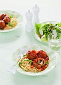 Meatballs with mozzarella and tomato sauce on a bed of spaghetti (Italy)