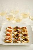 Crackers with various toppings served with white wine