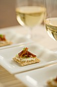Crackers topped with cheese, bacon, salmon and chives served with white wine