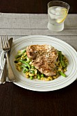 A pork chop with a bean salad and Parmesan cheese