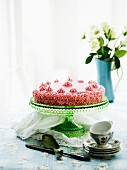 A pink buttercream cake on a cake stand