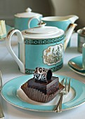 A petit four on a plate with turquoise tea crockery