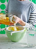 A woman sieving iced tea with lemon peel