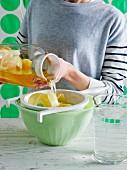 Frau giesst Eistee mit Zitronenschale durch Sieb