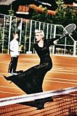 Junge Frau in schwarzem Abendkleid spielt Tennis