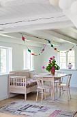 Stühle und Tisch rosa lackiert mit passender Sitzbank vor Fenster, ländliche Zimmerecke mit von Decke abgehängte Girlande