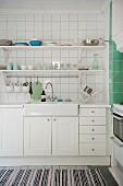 Küchenzeile mit Spülbecken und weissen Unterschränken vor gefliester Wand mit Ablagen