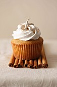 A chai cupcake on cinnamon sticks