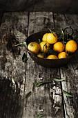 Mandarinen in einer Schüssel auf Holzuntergrund