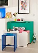 Eingeklappter, rollbarer, grüner Tisch mit untergeschobener weißer Sitzbank und Schublade; Stauraumlösungen mit platzsparendem Mobiliar