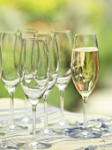 A glass of champagne standing next to empty champagne glasses