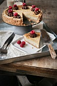 Vegan cheesecake with raspberries on a metal tray on wooden surface