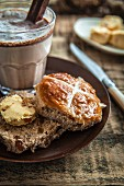 A hot cross bun served with cocoa