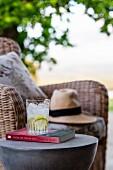 Erfrischungsgetränk auf Buch und Beistelltisch vor Korbsessel im Freien