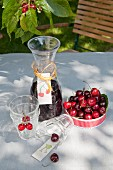 Carafe with hand-made label, glasses and dish of cherries