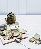Cooked artichokes on a wooden board with aioli and vinaigrette