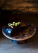 A slice of vegan chocolate cake with pistachio nuts