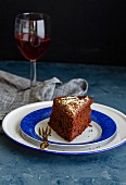 A slice of eggless chocolate cake on a plate with a glass of red wine