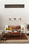 Sofa vor einer Backsteinwand mit drei Stierköpfen
