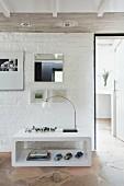 Modernes Regal vor einer weißen Backsteinwand auf Natursteinboden