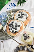 Blueberry tartlets and silver cutlery on table set for afternoon coffee