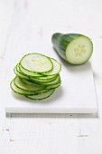 A piece of cucumber and a stack of cucumber slices