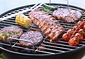 A beef steak, hamburgers, spare ribs, tomatoes and a corn cob on a barbecue