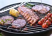 Rindersteak, Hamburger, Spareribs, Tomaten und Maiskolben auf dem Holzkohlengrill