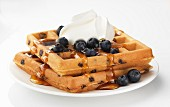 A blueberry waffle with cream and maple syrup