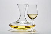 A glass carafe and a glass of white wine on a white surface