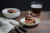 Dates wrapped in bacon served with a glass of beer