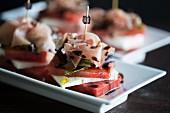 Türmchen aus Wassermelone und Schafskäse mit einer Scheibe Parmaschinken, Dressing aus Olivenöl und Balsamico