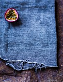 Half a passion fruit on a blue cloth