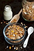 A bowl of muesli and a bottle of milk