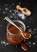 Salted caramel sauce in a jar and on a spoon