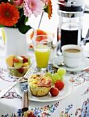 Frühstückstisch mit Obstsalat, Saft, Kaffee und pikantem Muffin