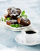Heart-shaped chocolate cakes with mint served with a cup of coffee