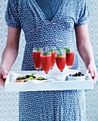A woman serving champagne cocktails with watermelon and grilled bread with tapenade on a tray