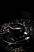 A black espresso cup with espresso beans