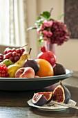 Aufgeschnittene Feigen auf Teller und grosse Obstschale mit verschiedenen Früchten